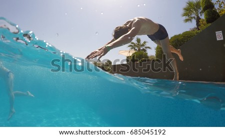 young man diving into a swimming pool
