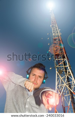 Young Man DJ with helmets or headphones sound or music, surrounded by effect of light and antenna or Telecommunication tower  - stock photo