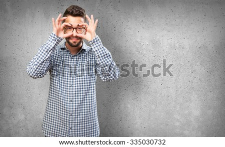 young man doing a glasses gesture - stock photo