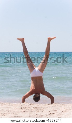 Young man doing a handstand  at the beach. - stock photo