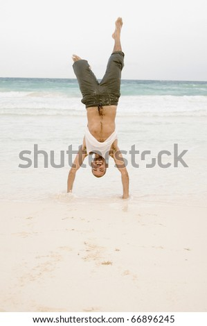 Young man doing a handstand on the beach