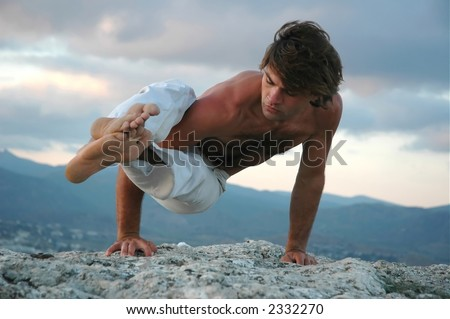 Young man doing an ashtavakrasana. Hand standing (variant) - stock photo
