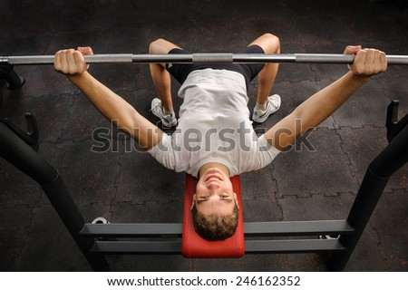 young man doing bench press workout in gym - stock photo
