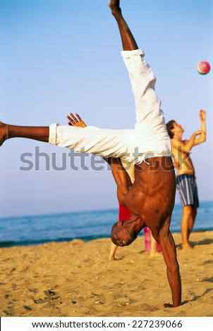 Young man doing handstand on the beach - stock photo