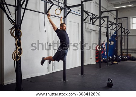 Young man doing kipping pull-ups exercise at gym - stock photo