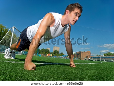Young man doing press ups  on the grass - stock photo