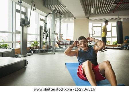 Young man doing sit-ups in the gym - stock photo