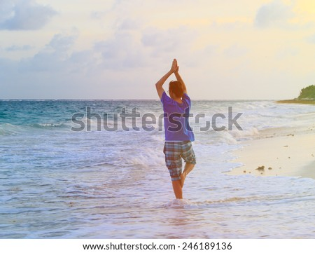 young man doing yoga at summer sunset beach