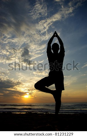 Young man doing yoga at the beach - stock photo