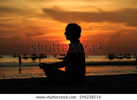 young man doing yoga on sunset tropical beach