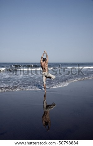 young man doing yoga on the beach, Goa, India