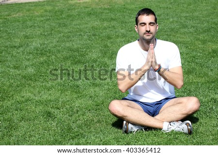 Young man doing yoga on the grass in seating position. - stock photo