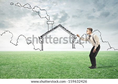 young man drawing an imaginary house - stock photo