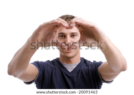 Young Man Drawing Heart with Hands - focus on eyes - stock photo