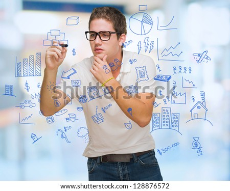Young Man Drawing Hierarchy Diagram, Indoors