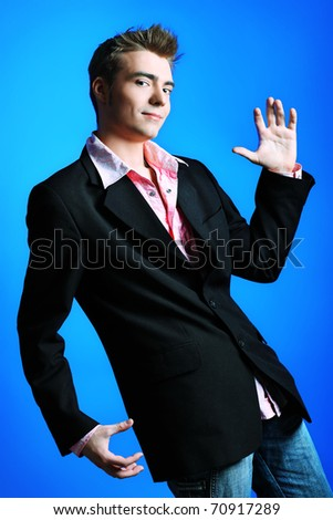 Young man dressed in rock'n'roll style, dancing over blue background. - stock photo
