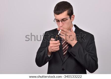young man dressed in tuxedo lighting cigarette in studio - stock photo