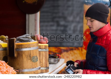 Young man dressed in warm winter clothing opening his wallet and making a purchase at an outdoor stall - stock photo