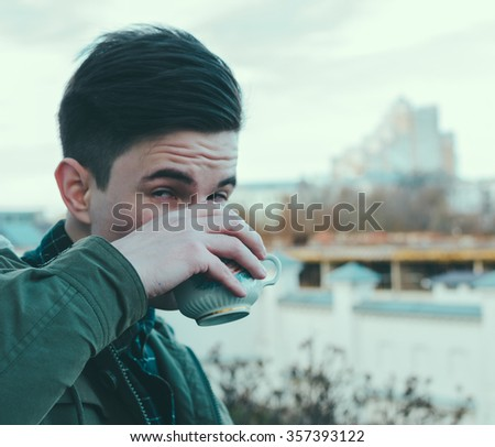 young man drink a coffee on the street