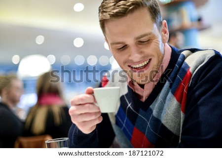 Young man drinking a coffee at the cafe - stock photo