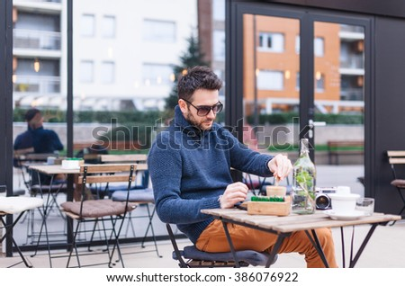 Young man drinking coffee at coffee shop garden - stock photo