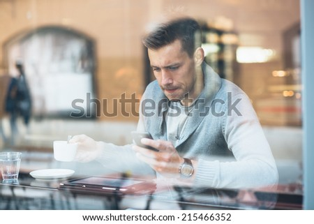 Young man drinking coffee in cafe and using phone - stock photo