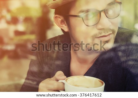 Young man drinking coffee inside cafe with sunrise - stock photo