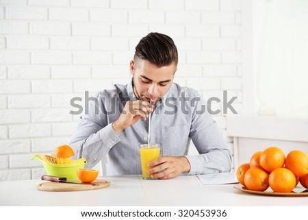 Young man drinking orange juice - stock photo