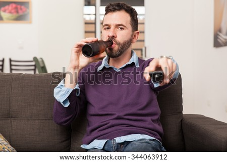 Young man drinking some beer from a bottle and changing the TV channel at home - stock photo