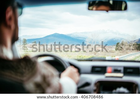 Young man drives a car in mountains. Mountains are seen through the windscreen - stock photo