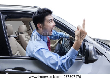 Young man driving a car and looks angry, screaming and showing middle finger - stock photo