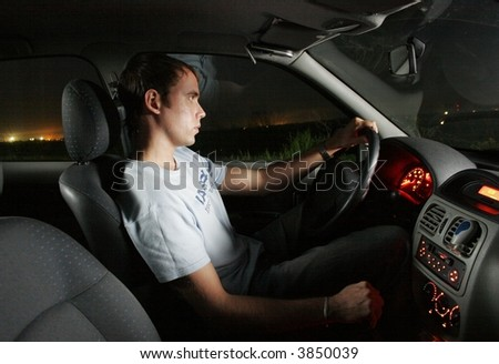 Young man driving a car at night. Interior of a car. - stock photo