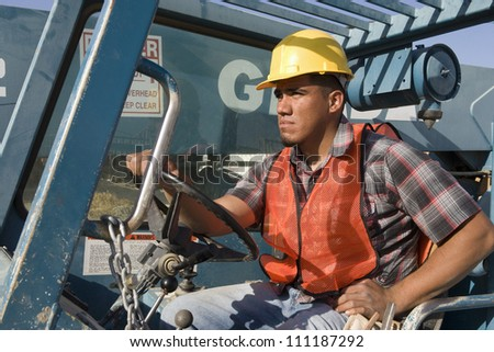Young man driving bulldozer at construction site