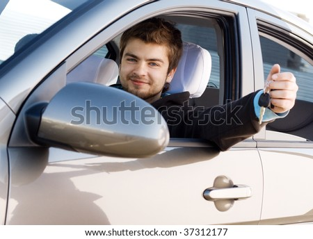 Young man driving his new car, holding out keys - stock photo