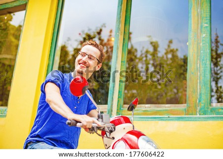 Young man driving his rent motorbike in bali - stock photo