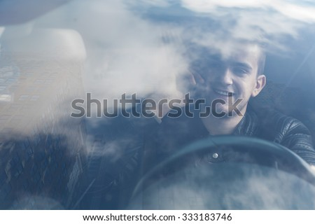 young man driving through the city an talking on the phone. Buildings and sky reflecting in the mir - stock photo