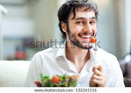 Young man eating a healthy salad - stock photo