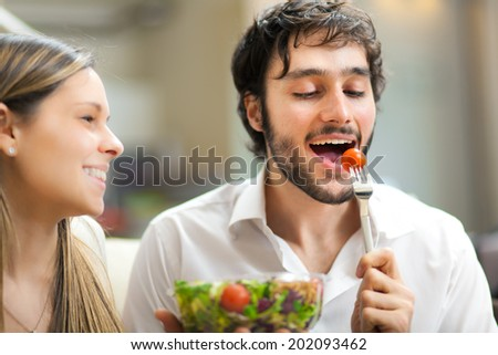 Young man eating a salad - stock photo
