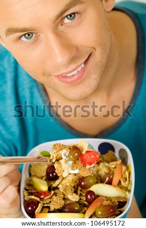 Young man eating cereals in the morning - stock photo
