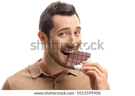 Young man eating chocolate isolated on white background