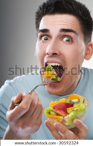Young man eating fruit close up shoot