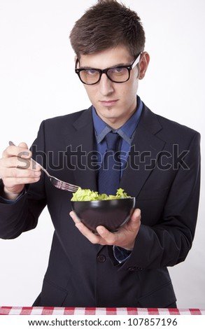 Young man eating salad. - stock photo