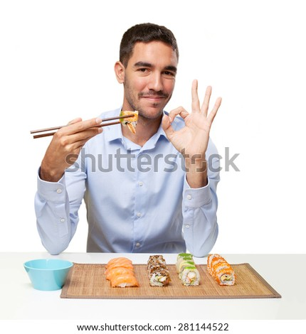 Young man eating sushi - stock photo