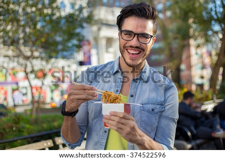 Young man eating take away noodles on the street - stock photo