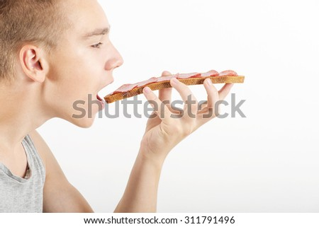 Young man eats big snack, opened mouth, side view - stock photo