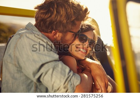 Young man embracing and kissing his beautiful girlfriend while on a road trip. Romantic couple in a car on summer holiday. - stock photo