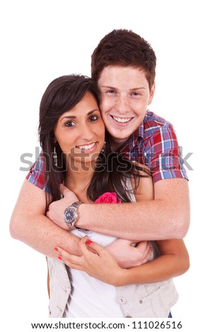 Young man embracing his girlfriend while both of them are watching the camera - stock photo