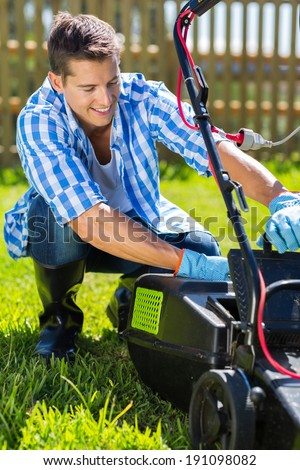 young man emptying lawnmower grass catcher after mowing the lawn - stock photo