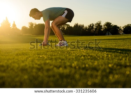 Young man engaged in sports in the street. Sports ground on nature. Guy shakes his muscles on the nature. Sports lifestyle. - stock photo