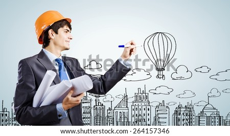 Young man engineer drawing sketches of construction project - stock photo